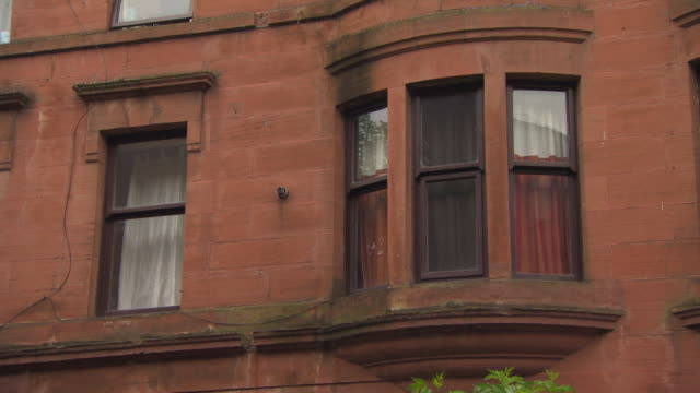 shadows of trees are reflected in tenement building windows, govan, glasgow, scotland. - stone object stock videos and b-roll footage