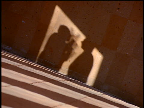 CANTED shadows of two men arguing / tilt up PAN to businessmen arguing