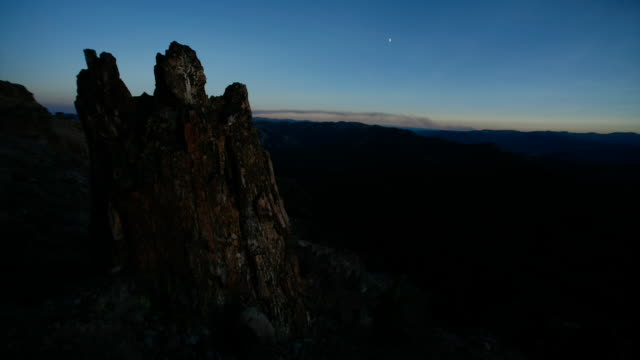 Shadows pass over a rocky outcrop as night falls.