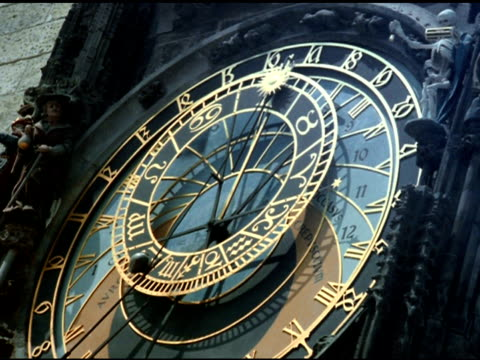 Shadows pass over ornate clock face of Orloj astronomical clock, Prague
