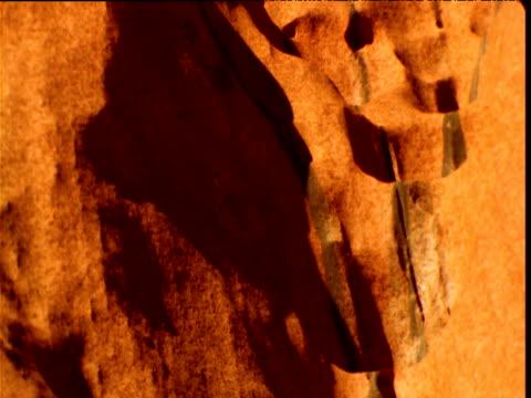 shadows recede on glowing orange sandstone of uluru in outback, northern territory, australia - sandstone stock videos & royalty-free footage