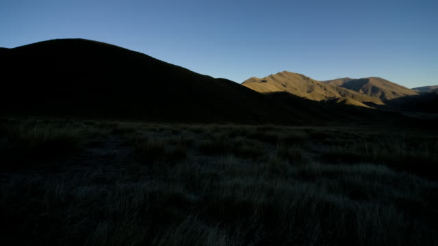 shadows retreat from the hills of lindis pass. - otago region stock videos & royalty-free footage