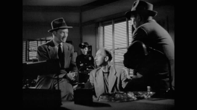vídeos de stock e filmes b-roll de 1948 a shady character is questioned by detectives - com sombra