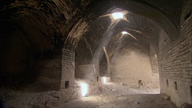 ws pan tu shafts of sunlight coming through holes in ceiling of caravanserai, iran - inn stock videos & royalty-free footage