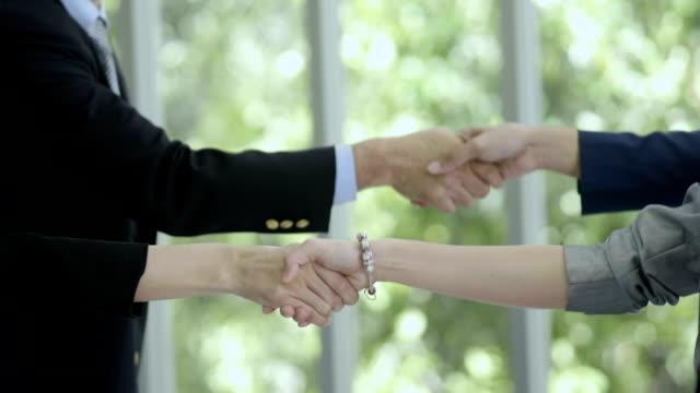 vidéos et rushes de serrer la main. - quatre personnes
