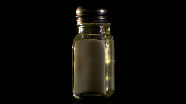 a shaker of salt rotates. - salt shaker stock videos and b-roll footage