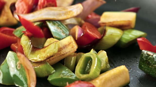 SLO MO Shaking a pan with stir frying vegetables