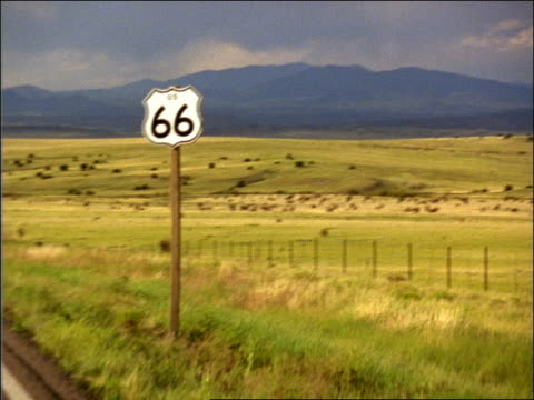 vidéos et rushes de shaky car point of view past route 66 road sign on country road on plains / mountains in background - route 66