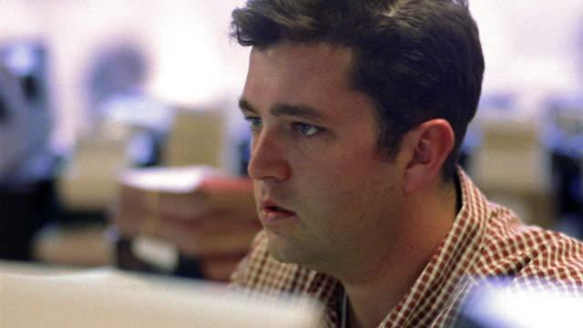 Shaky close up worried man looking at various computer monitors and talking in office