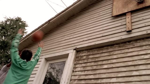 vídeos y material grabado en eventos de stock de shaky low angle medium shot kids playing basketball with hoop attached to garage - canasta de baloncesto