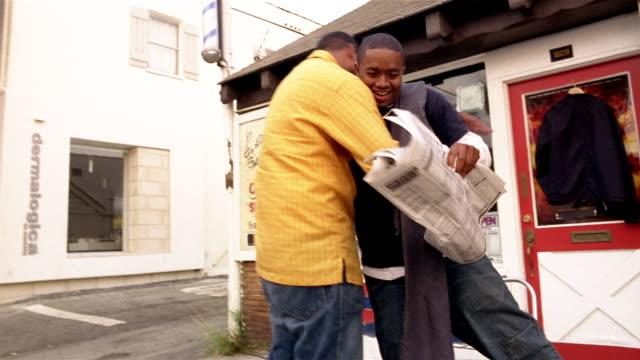 Shaky low angle medium shot man reading newspaper / standing up and greeting friend / Santa Monica, California