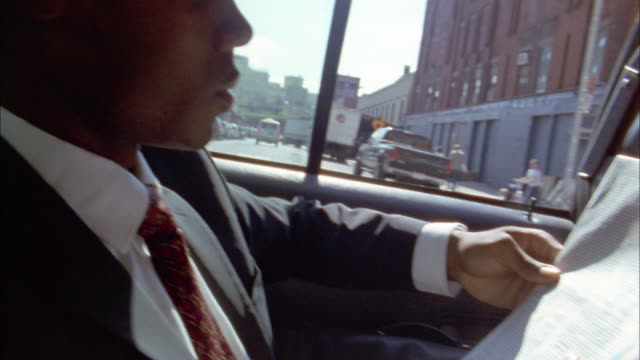 Shaky medium shot Black businessman reading newspaper in taxicab
