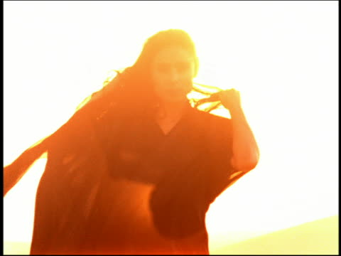 Shaky medium shot DEFOCUS woman in desert walking toward camera and lowering veil w/yellow sunflares