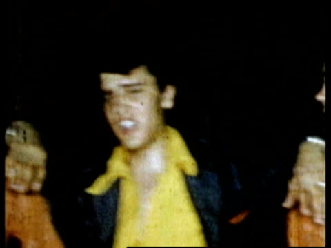 stockvideo's en b-roll-footage met 1955 shaky medium shot elvis presley backstage clowning with arms around scotty moore and bill black / texas - 1955