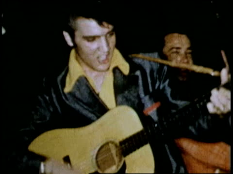 1955 shaky medium shot Elvis Presley playing guitar and singing on stage with Scotty Moore + Bill Black / Texas