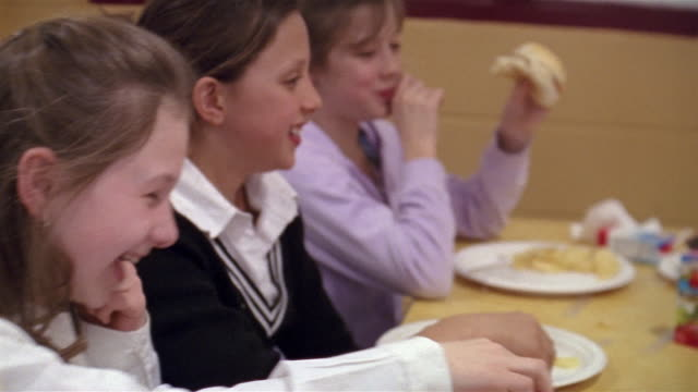 Shaky medium shot girls eating at school cafeteria/ Goram, Maine