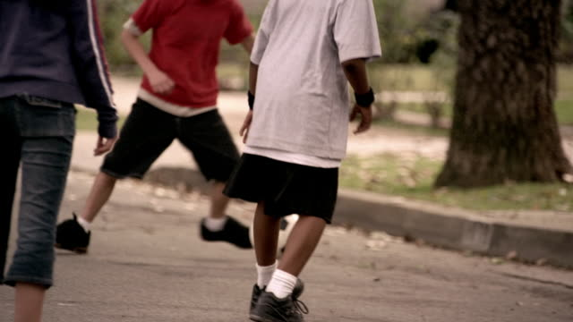 shaky medium shot kids playing soccer in the street - kicking stock videos & royalty-free footage