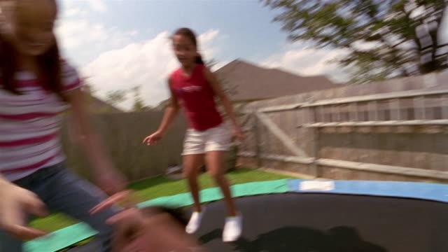 Shaky medium shot pan children bouncing on trampoline in backyard