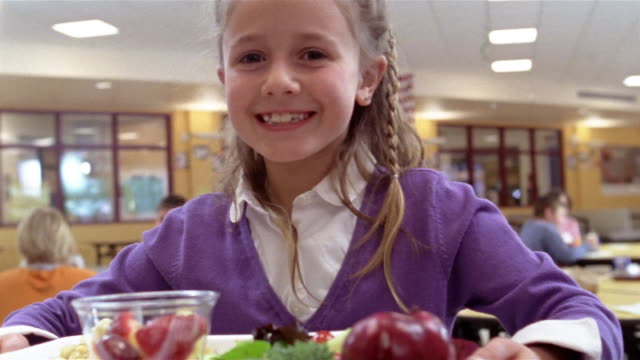 vídeos de stock e filmes b-roll de shaky medium shot pan girl holding school lunch tray, smiling and looking at camera/ goram, maine - merenda escolar