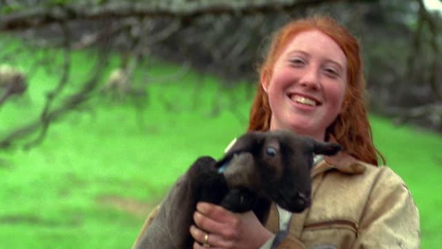 shaky medium shot portrait red-headed girl holding lamb and smiling outdoors / california - endast en tonårsflicka bildbanksvideor och videomaterial från bakom kulisserna