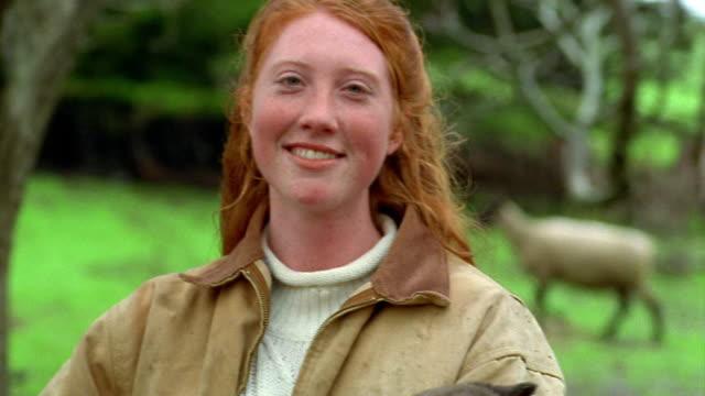Shaky medium shot portrait red-headed teen girl holding lamb and smiling outdoors / California