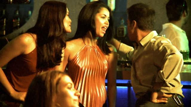 shaky medium shot zoom in zoom out 2 women talking to man at bar in nightclub - 男性と複数の女性点の映像素材/bロール