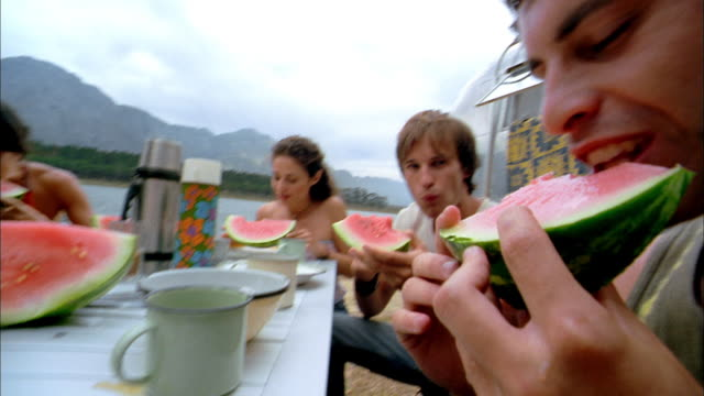 shaky pan men and women eating watermelon around table on lake shore w/mountains in background - schwenk stock-videos und b-roll-filmmaterial