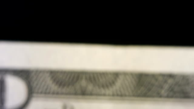 Shaky shot of the $100 symbol on the hundred dollar bill