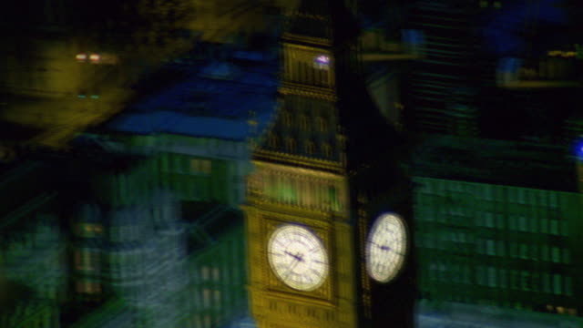 Shaky slow motion aerial point of view around Big Ben at night / London