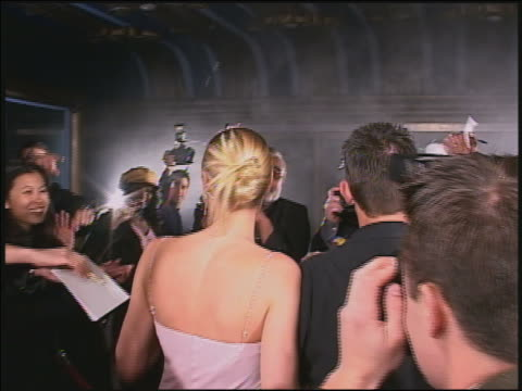 Shaky video camera point of view famous couple posing and waving in crowd of groupies + press / AUDIO