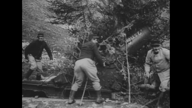 vídeos de stock, filmes e b-roll de [shaky video] group of soldiers pitching coins artillery piece in background / austrian warplane flying overhead / soldiers cover artillery piece... - cultura austríaca