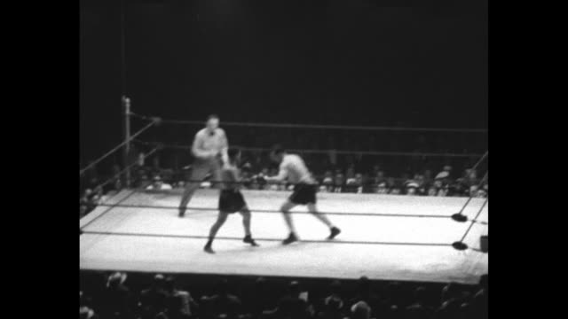 """[shaky video] title card: """"walker battles sharkey to draw - middleweight boxing champion and big heavyweight mix in furious 15-round fight at new... - 格闘技リング点の映像素材/bロール"""