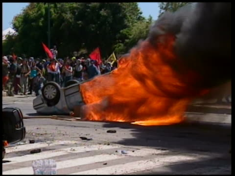 2001 shaky wide shot overturned car in flames / g8 summit / genoa italy - g8 summit stock videos & royalty-free footage