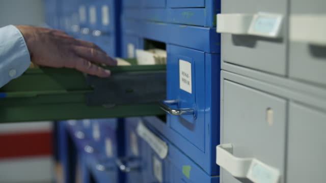 stockvideo's en b-roll-footage met shallow dof shot of a man browsing through an index card filing cabinet - bbc archives