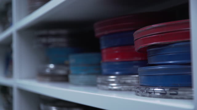 shallow dof shot of a man selecting multicoloured film cans from a shelf - film stock videos & royalty-free footage