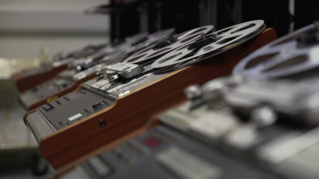 stockvideo's en b-roll-footage met shallow dof shot of a row of 'struder' reel to reel film players - bbc archives
