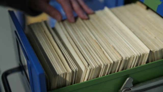 shallow dof shot of a women selecting an index card from a filing cabinet - scegliere video stock e b–roll