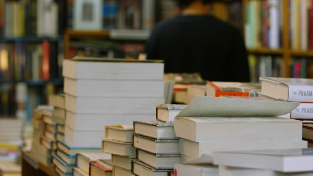 shallow dof shot of customers browsing in a bookshop with a pile of books in the foreground - saggezza video stock e b–roll