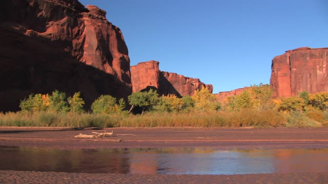 WS Shallow river flowing past red cliffs/ Canyon de Chelly National Monument, Arizona