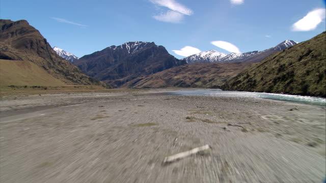 vídeos de stock, filmes e b-roll de a shallow river flows through a valley toward rugged mountains. available in hd. - erodido