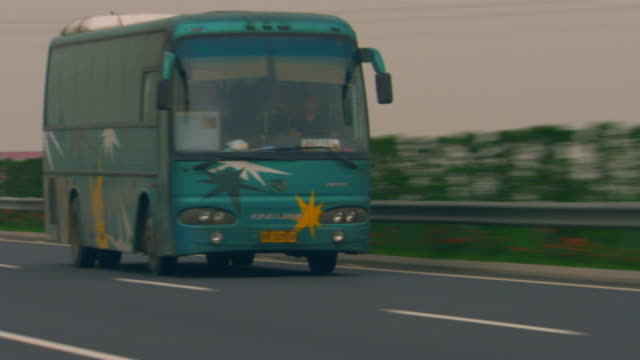 shanghai, chinabus passes by - tour bus stock videos and b-roll footage