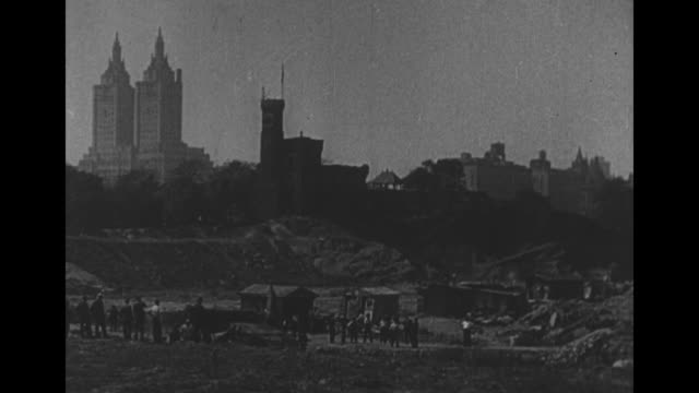 shanties in central park with twin towers of san remo apartments in the distance / men in shirtsleeves with one sweeping threshold of shanty / note... - upper west side manhattan stock videos and b-roll footage