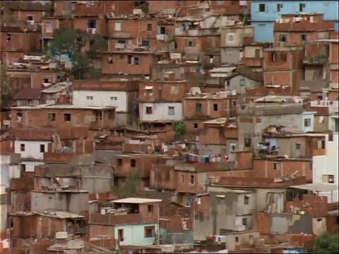 vídeos de stock e filmes b-roll de shanty houses stretch up a hillside. - favela