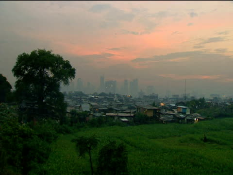 Shanty town in foreground luxury high rises in distance on skyline Manila Philippines