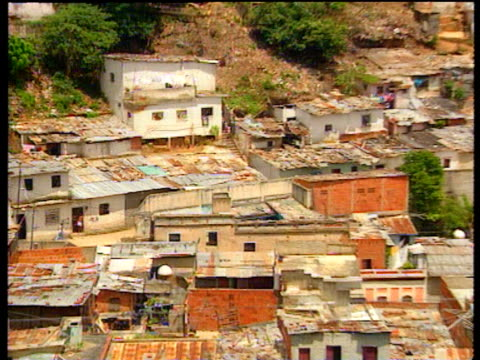 Shanty town onShanty town zoom in girl holding rail Venezuela