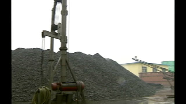 Shanxi Province EXT Chinese flag flying on top of mining equipment in thick smog Piles of coal at processing plant PAN Close up of coal on conveyor...