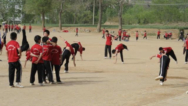 shaolin monks practice gymnastics outdoors. - カンフー点の映像素材/bロール