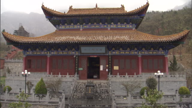 a shaolin practitioner performs sword maneuvers in front of a temple. - pagoda stock videos & royalty-free footage