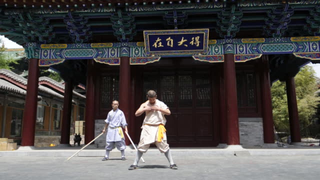 a shaolin student breaks a wood bar across another student's arm as he demonstrates a kung-fu skill. - カンフー点の映像素材/bロール