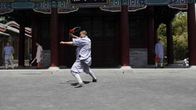 a shaolin student demonstrates a weapon, and is then joined by peers with different weapons. - カンフー点の映像素材/bロール
